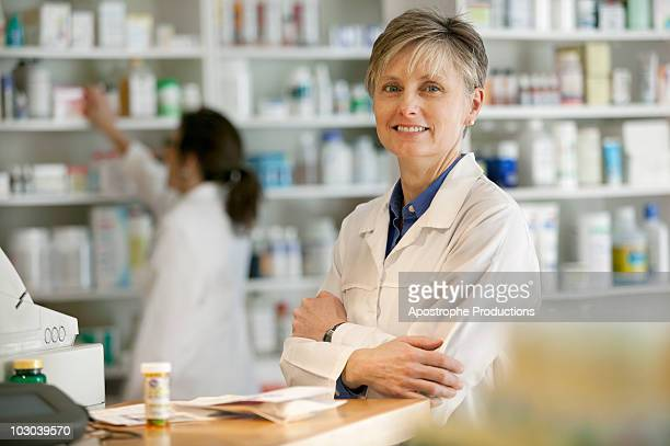 pharmacists at counter of retail pharmacy - blacksburg stock pictures, royalty-free photos & images
