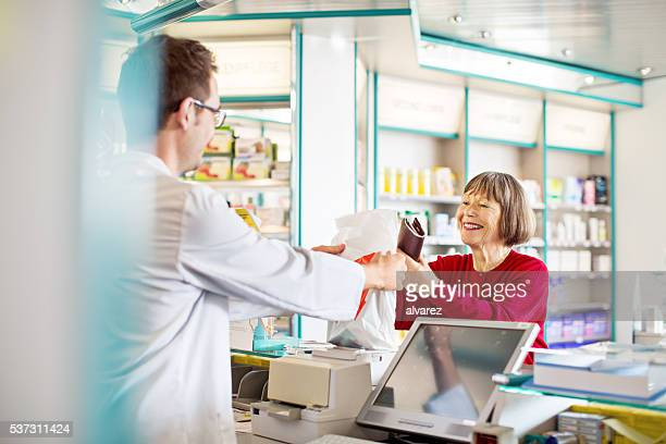 Pharmacist's giving prescription medication to customer