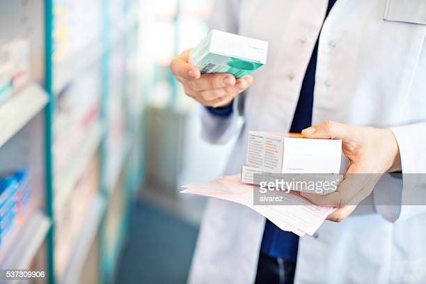 pharmacist's hands taking medicines from shelf - medicijnen stockfoto's en -beelden