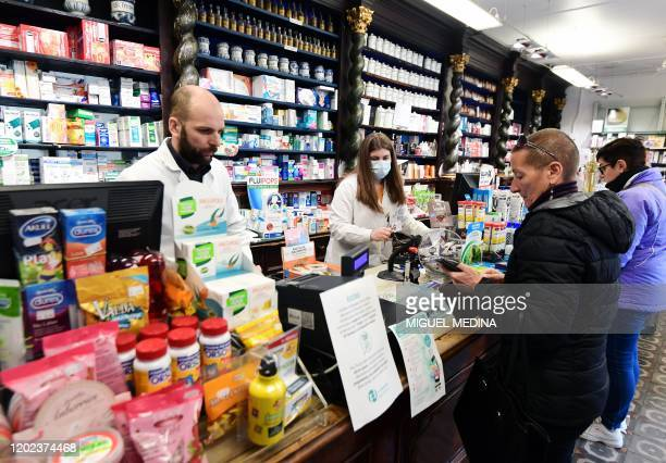 Pharmacists one wearing a protective respiratory mask tend to customers in Codogno southeast of Milan on February 22 2020 An Italian man became the...