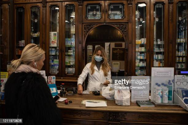 A pharmacists serves a customer on March 11 2020 in Milan Italy The Italian Government has strengthened up its quarantine rules shutting all...