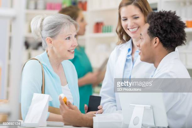 Pharmacists talk with senior customer