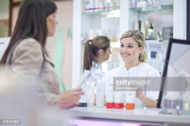 Pharmacists talking to customer