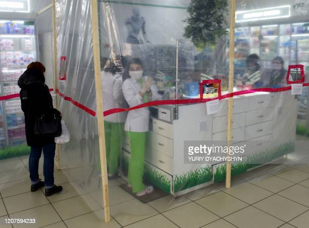 TOPSHOT Pharmacists wearing face masks are seen behind polyethylene membrane set around the counter in a pharmacy in the western Ukrainian city of...