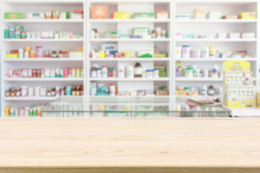 Pharmacy drugstore counter table with blur abstract backbround with medicine and healthcare product on shelves 950928592