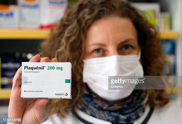 A pharmacy employee wearing a protective mask shows a box of Plaquenil on March 27 2020 in Paris France French Minister of Health Olivier Veran in a...