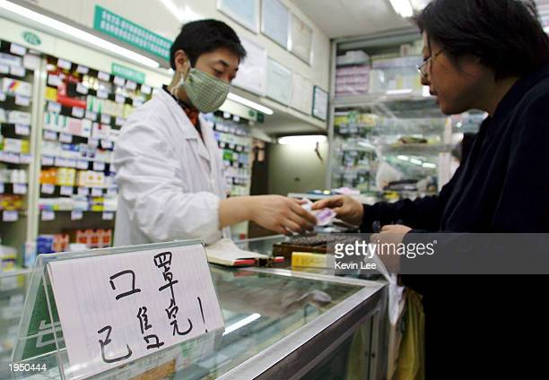 Pharmacy employee wears a surgical-type mask to protect himself from the deadly SARS virus April 25, 2003 in downtown Shanghai, China. The Chinese...
