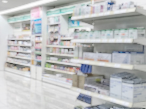 Pharmacy store or drugstore blur background with drug shelf and blurry pharmaceutical products, cosmetic and medication supplies on shelves inside retail shop interior 1005718152