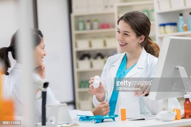 Pharmacy tech talks with pharmacist about a customer's order