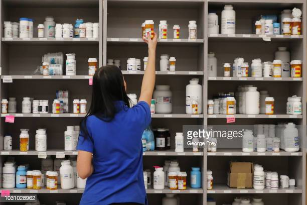 A pharmacy technician grabs a bottle of drugs off a shelve at the central pharmacy of Intermountain Heathcare on September 10 2018 in Midvale Utah...
