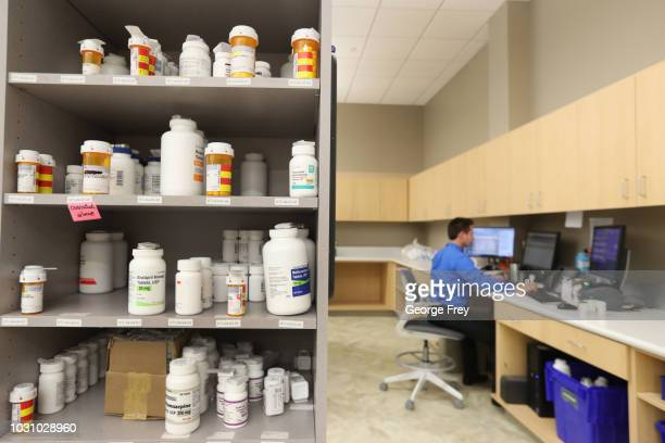 A pharmacy technician works on a computer as drug bottles sit on shelves at the central pharmacy of Intermountain Heathcare on September 10 2018 in...