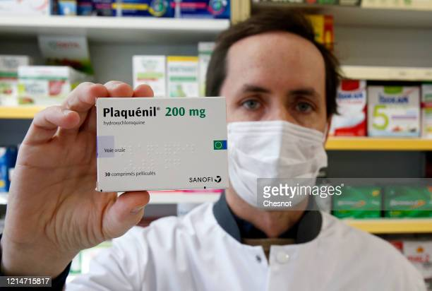 A pharmacy worker wears a protective mask shows a box of Plaquenil on March 25 2020 in Paris France The hydroxychloroquine marketed under the name of...
