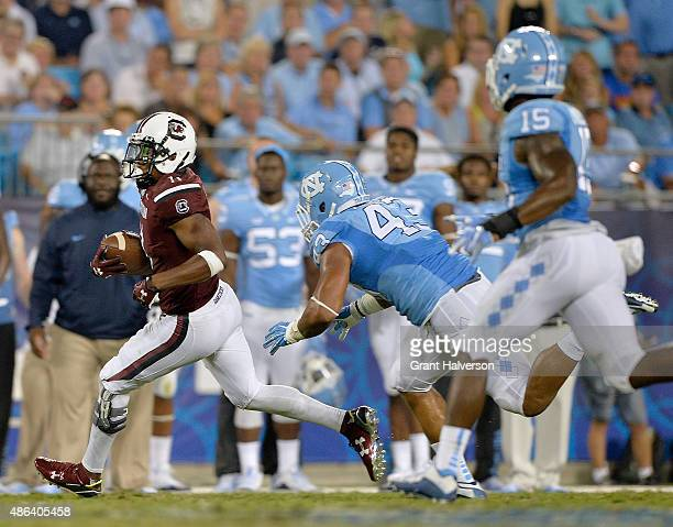 Pharoh Cooper of the South Carolina Gamecocks breaks away from Jessie Rogers of the North Carolina Tar Heels during their game at Bank of America...