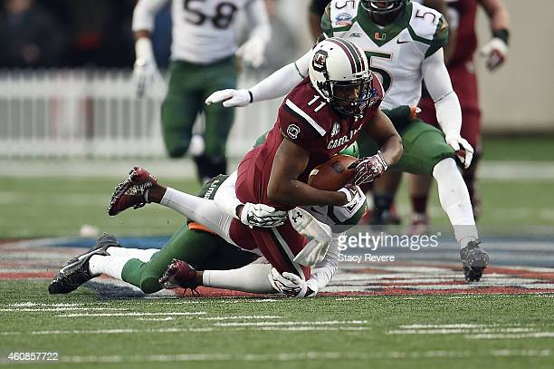 Pharoh Cooper of the South Carolina Gamecocks is brought down by Corn Elder of the Miami Hurricanes during the second quarter of the Duck Commander...