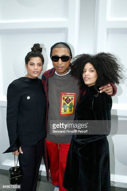 Pharrell Williams standing between Musical Group Ibeyi LisaKainde Diaz and her sister Naomi Diaz attend the Chanel show as part of the Paris Fashion...