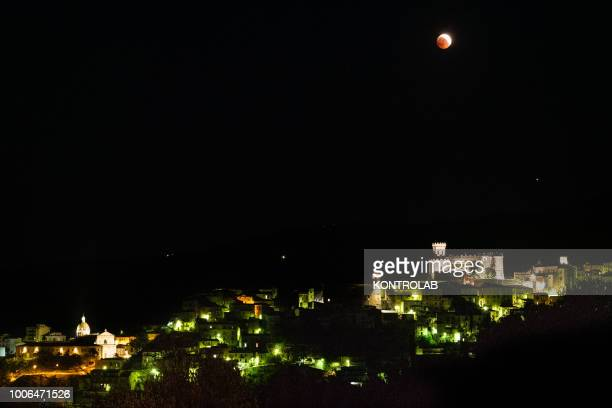 A phase of the total eclipse of the moon which turns red on the Castle of Corigliano Calabro in Calabria southern Italy The lunar eclipse is...