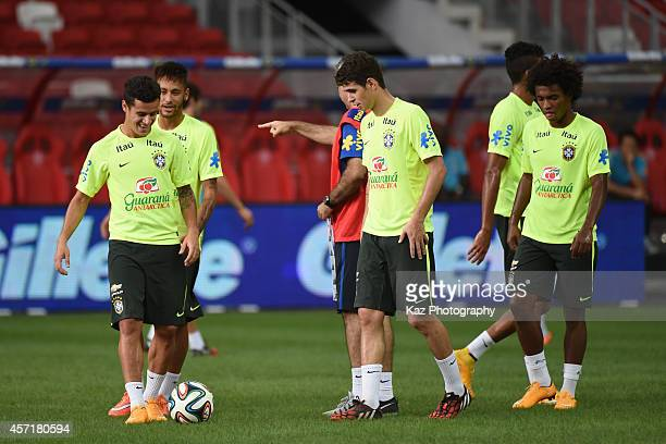 Phelippe Coutinho of Brazil enjoys the chat with his team mates Oscar Willian and Neymar of Brazil during the training session ahead of international...