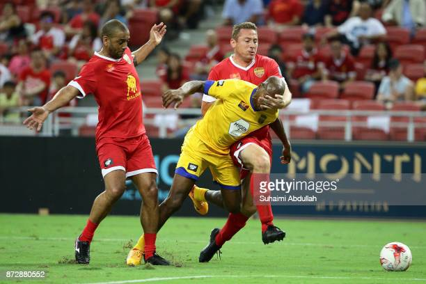 Phil Babb and Jan Kromkamp of Liverpool Masters challenge Luis Boa Morte of Arsenal Masters during the Battle of the Masters at National Stadium on...