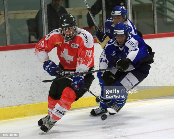 Phil Baltisberger of Switzerland clears the puck in front of Joose Antonen of Finland during the U-18 Four Nations Cup tournament on November 9, 2012...