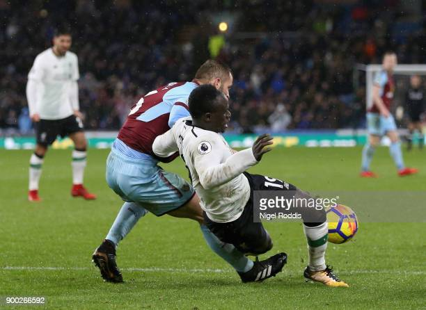 Phil Bardsley of Burnley tackles Sadio Mane of Liverpool during the Premier League match between Burnley and Liverpool at Turf Moor on January 1 2018...