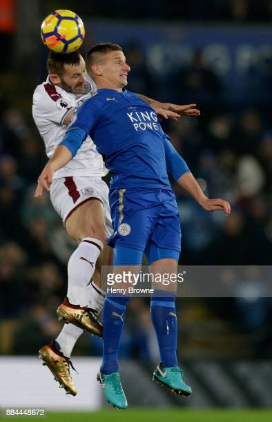 Phil Bardsley of Burnley wins a header over Marc Albrighton of Leicester City during the Premier League match between Leicester City and Burnley at...