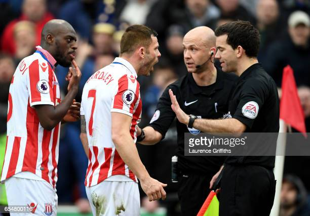 Phil Bardsley of Stoke City argues with referee Anthony Taylor and his assistant during the Premier League match between Stoke City and Chelsea at...