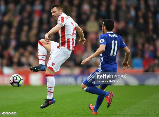 Phil Bardsley of Stoke City controls the ball while under pressure from Pedro of Chelsea during the Premier League match between Stoke City and...
