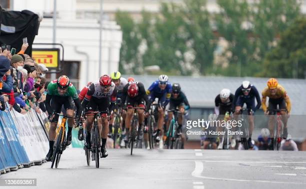 Phil Bauhaus of Germany and Team Bahrain Victorious green points jersey and Alexander Kristoff of Norway and UAE Team Emirates sprint to win during...