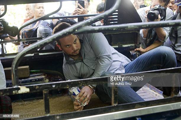 Phil Blackwood a New Zealand bar manager is pictured in the back of a vehicle surrounded by the media as he attends a court hearing in Yangon on...
