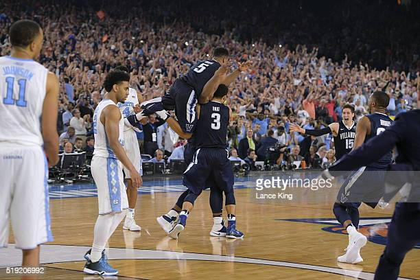Phil Booth and Josh Hart celebrate with Kris Jenkins of the Villanova Wildcats following their victory against the North Carolina Tar Heels during...