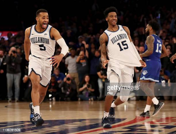 Phil Booth and Saddiq Bey of the Villanova Wildcats celebrates the 7472 win as Myles Powell of the Seton Hall Pirates walks off the court to claim...