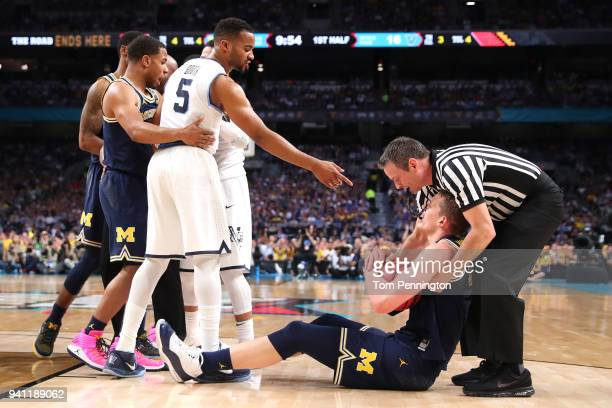 Phil Booth of the Villanova Wildcats and Moritz Wagner of the Michigan Wolverines exchange words after competing for a loose ball in the first half...