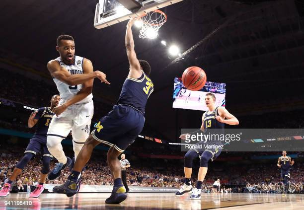 Phil Booth of the Villanova Wildcats attempts to save the ball against Zavier Simpson of the Michigan Wolverines in the second half during the 2018...