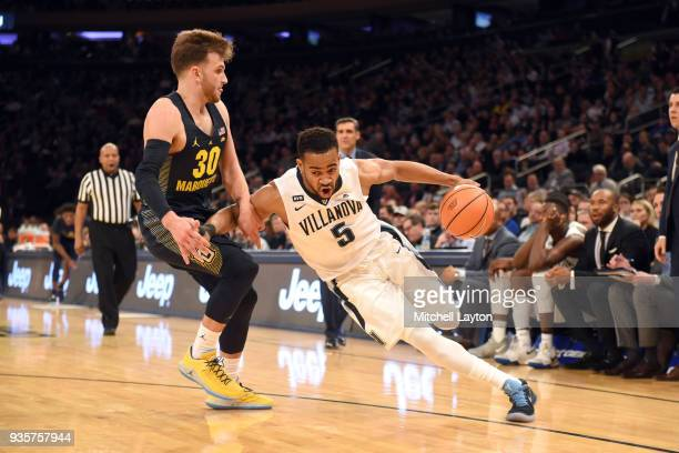 Phil Booth of the Villanova Wildcats dribbles by Andrew Rowsey of the Marquette Golden Eagles during the quarterfinal round the Big East Men's...