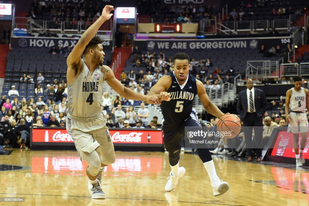 Phil Booth #5 of the Villanova Wildcats dribbles by Jagan Mosely #4 of the Georgetown Hoyas during a college basketball game at the Capital One Arena on January 17, 2018 in Washington, DC.