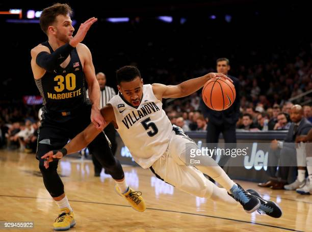Phil Booth of the Villanova Wildcats drives around Andrew Rowsey of the Marquette Golden Eagles in the second half during quarterfinals of the Big...