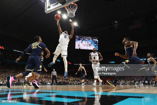 Phil Booth of the Villanova Wildcats drives to the basket against MuhammadAli AbdurRahkman of the Michigan Wolverines in the first half during the...