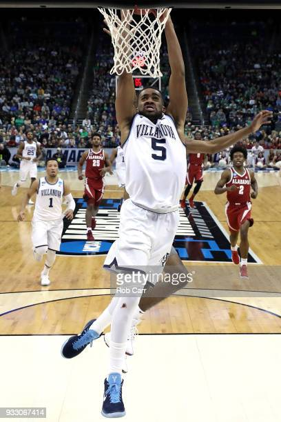 Phil Booth of the Villanova Wildcats dunks the ball against John Petty of the Alabama Crimson Tide during the second half in the second round of the...