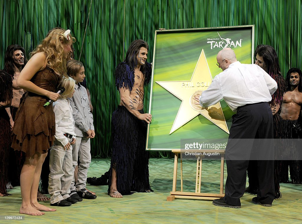 Phil Collins and both sons Matthew Collins and Nicholas Collins, Elisabeth Huebert (Jane) and Alexander Klaws are watching a handprint honouring Phil Collins during Tarzan Musical 3rd anniversary at Theatre 'Neue Flora' on October 22, 2011 in Hamburg, Germany.