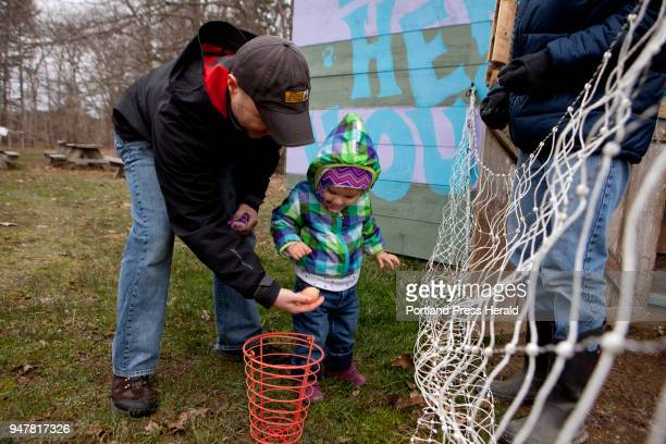 Phil Daigle of Yarmouth helps his daughter Natalie gently put a freshly laid egg into the collecting basket during the First Time Farmers program at...