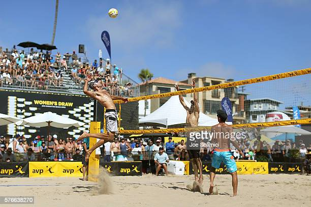 Phil Dalhausser jumps to spike the ball over the net as Nick Lucena readies to defend during their quarter final match against Tri Bourne and John...