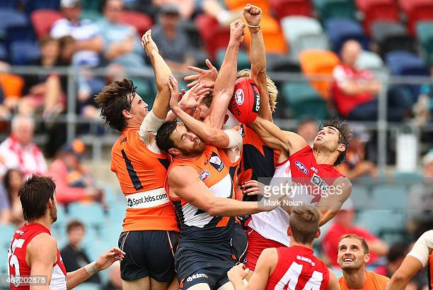 Phil Davis and Shane Mumford of the Giants and Sam Naismith of the Swans contest a mark during the NAB Challenge AFL match between the Greater...