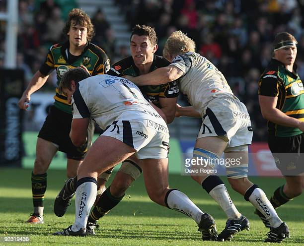 Phil Dowson of Northampton is tackled by Gavin Kerr and David Seymour during the Guinness Premiership match between Northampton Saints and Sale...