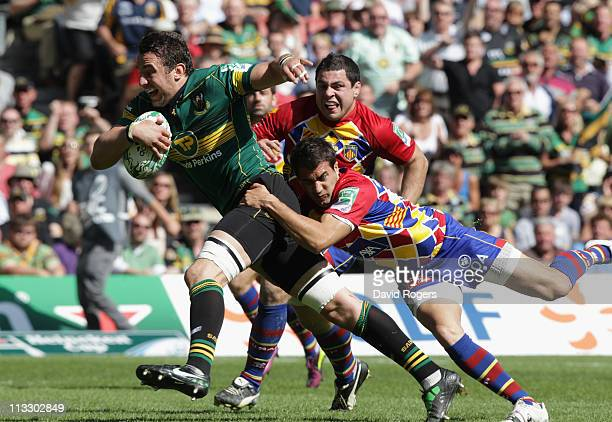 Phil Dowson of Northampton is tackled by Jerome Porical during the Heineken Cup semi final match between Northampton Saints and Perpignan at stadium...