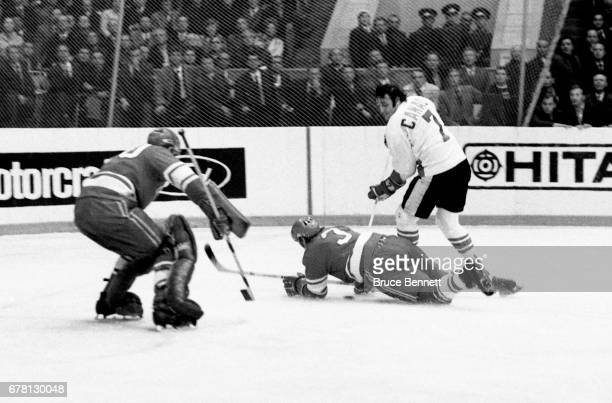 Phil Esposito of Canada knocks down Vladimir Lutchenko as goalie Vladislav Tretiak of the Soviet Union follows the play during a game in the 1972...