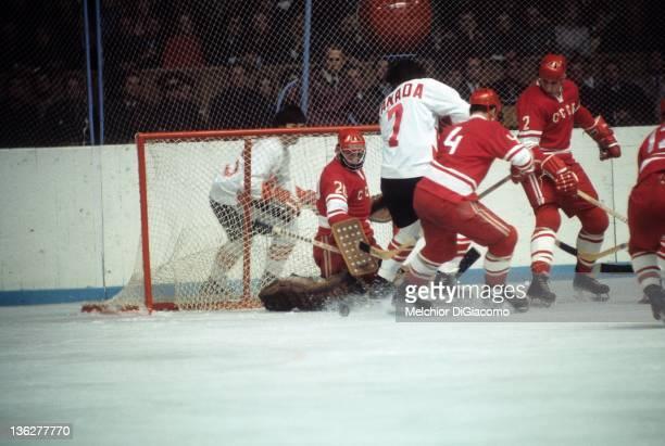 Phil Esposito of Canada tries to score as goalie Vladislav Tretiak looks to make the save as Viktor Kuzkin and Alexander Gusev help on defense during...