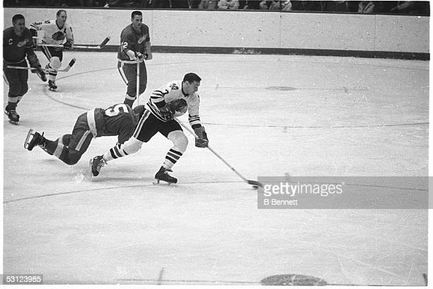 Phil Esposito of the Chicago Blackhawks skates on the ice with the puck as Doug Harvey of the Detroit Red Wings defends during an NHL game circa 1967...