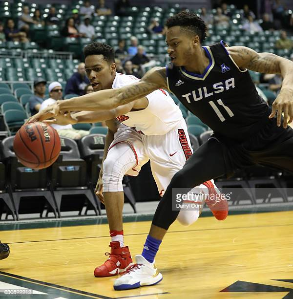 Phil Fayne of the Illinois State Redbirds and Pat Birt of the Tulsa Golden Hurricane lunge for a loose ball during the first half of the Diamond Head...