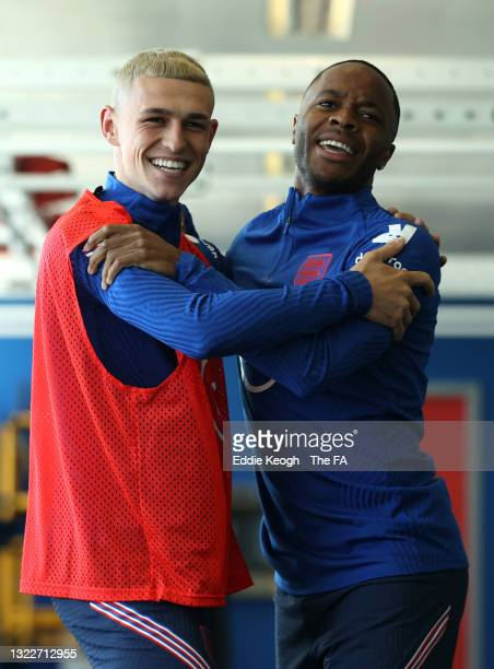 Phil Foden and Raheem Sterling of England share a joke during training at St George's Park on June 09, 2021 in Burton upon Trent, England.
