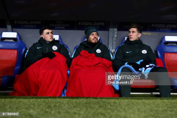 Phil Foden David Silva and John Stones all of Manchester City look on from the substitutes bench during the UEFA Champions League Round of 16 First...